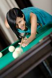 Woman playing billiard Stock Images