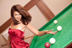 Woman playing billiards Stock Images