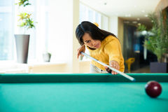 Woman playing billiards Stock Photography