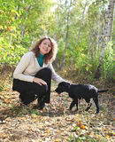 Woman playing with black labrador retriever puppy Royalty Free Stock Image