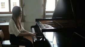 Woman playing the black piano on the background of the window in slow motion stock video
