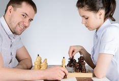 Woman playing black pieces in chess against the grinning men Royalty Free Stock Photos