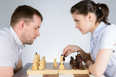 Woman playing the black pieces in chess against men Stock Image