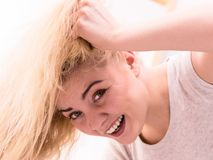 Woman playing with blonde hair. Happy woman playing with blonde hair. Positive clean female after taking a shower feeling clean and relaxed. Unusual crazy bottom stock images