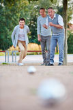 Woman playing boule with group of seniors Royalty Free Stock Images