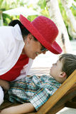 Woman playing with boy. A closeup view of a woman wearing a red hat, playing with boy in a lounge chair outdoors Royalty Free Stock Photography