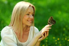 Woman playing with a butterfly Stock Photography