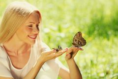 Woman playing with a butterfly Royalty Free Stock Image