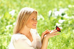 Woman playing with a butterfly Stock Images