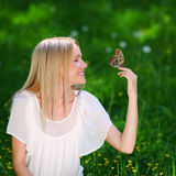 Woman playing with a butterfly Stock Photo