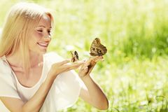 Woman playing with butterfly Stock Photo
