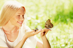 Woman playing with butterfly Royalty Free Stock Photos