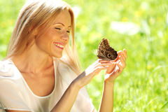 Woman playing with a butterfly Royalty Free Stock Photo