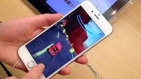 Woman playing car racing game on new iphone. Woman playing car racing game inside Apple store stock video footage