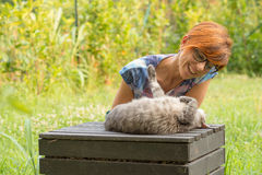 Woman playing with cat outdoors in green home garden Stock Photo