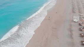 Woman playing catch with her Tibetan terrier dog along the beach, aerial drone view. Woman playing with her Tibetan terrier dog on the beach in the morning on a stock video footage