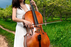 Woman playing the cello. Woman in white dress playing the cello close up in the garden stock image