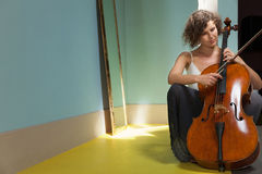Woman playing the cello. Portrait of young cellist, interior stock images
