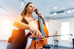 Woman playing cello. Young woman playing a cello stock photos