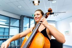 Woman playing cello. Young woman playing a cello stock image