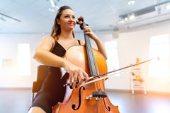 Woman playing cello. Young woman playing a cello stock photography