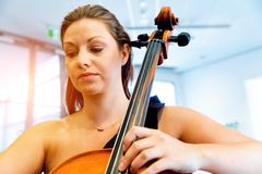 Woman playing cello. Young smiling woman playing cello royalty free stock image