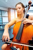Woman playing cello. Young smiling woman playing cello stock photo