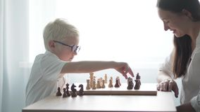 Mom and son play chess at the table in the room. A woman is playing chess with a boy wearing glasses. The boy albino in a white rush makes a move