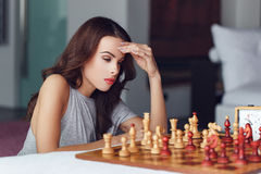 Woman playing chess indoor and thinking Royalty Free Stock Images
