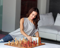 Woman playing chess indoor and thinking position Royalty Free Stock Photos