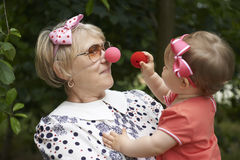 Woman is playing clowns with her little granddaugh Stock Images