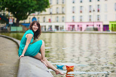 Woman playing with colorful paper boats on Canal Saint Martin in Paris, France Royalty Free Stock Photos