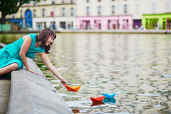 Woman playing with colorful paper boats on Canal Saint Martin in Paris, France Stock Photos