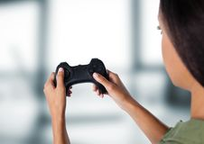 woman playing with computer game controller with bright blurred background Royalty Free Stock Photography