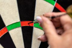 Woman playing dart, professional steeldart sport, closeup dartboard and hand royalty free stock photo