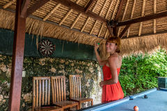 Woman playing darts in the tropical cafe of Nusa Lembongan, Bali, Indonesia. Stock Photos