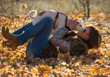 Woman playing with the dog. In the autumn park stock photography