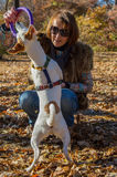 Woman playing with dog in autumn park Royalty Free Stock Photo