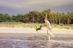 Woman playing with dog on beach Stock Photography