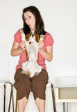 Woman playing with dog in waiting room Stock Photos