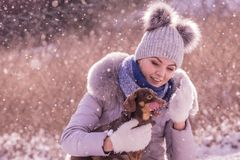 Woman playing with dog during winter stock photo