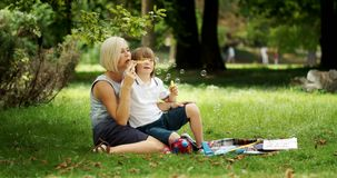 Woman Playing with Down Boy. Young blonde woman playing with autistic boy in park, playing with soap bubbles and sitting on green grass stock video footage