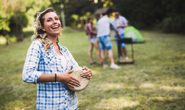 Woman playing drums having fun in nature. Woman playing drums having bbq  fun in nature with friends Royalty Free Stock Image