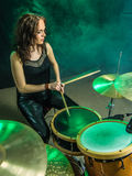 Woman playing drums onstage. Photo of a beautiful woman playing her drum set on stage Stock Image