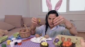 Woman playing with Easter eggs. In room