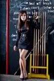 Woman playing eight ball. Beautiful woman  in short black dress playing in a pool room with eight ball cues Royalty Free Stock Photos