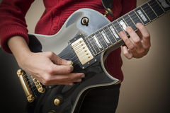 Woman Playing Electric Guitar. Woman Playing Black Electric Guitar Royalty Free Stock Photography