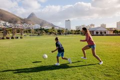 Mother and son playing football in park. Woman playing football with her son in a playfield. Family on a day out playing football in park Stock Image