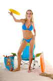 Woman Playing Frisbee On Beach. Young blond fashion model wearing a azure blue bikini throwing a Frisbee on the beach Royalty Free Stock Images