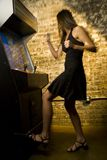 Woman playing game. Woman in a black dress playing with an arcade game machine and looking thrilled, excited and victorious Stock Images
